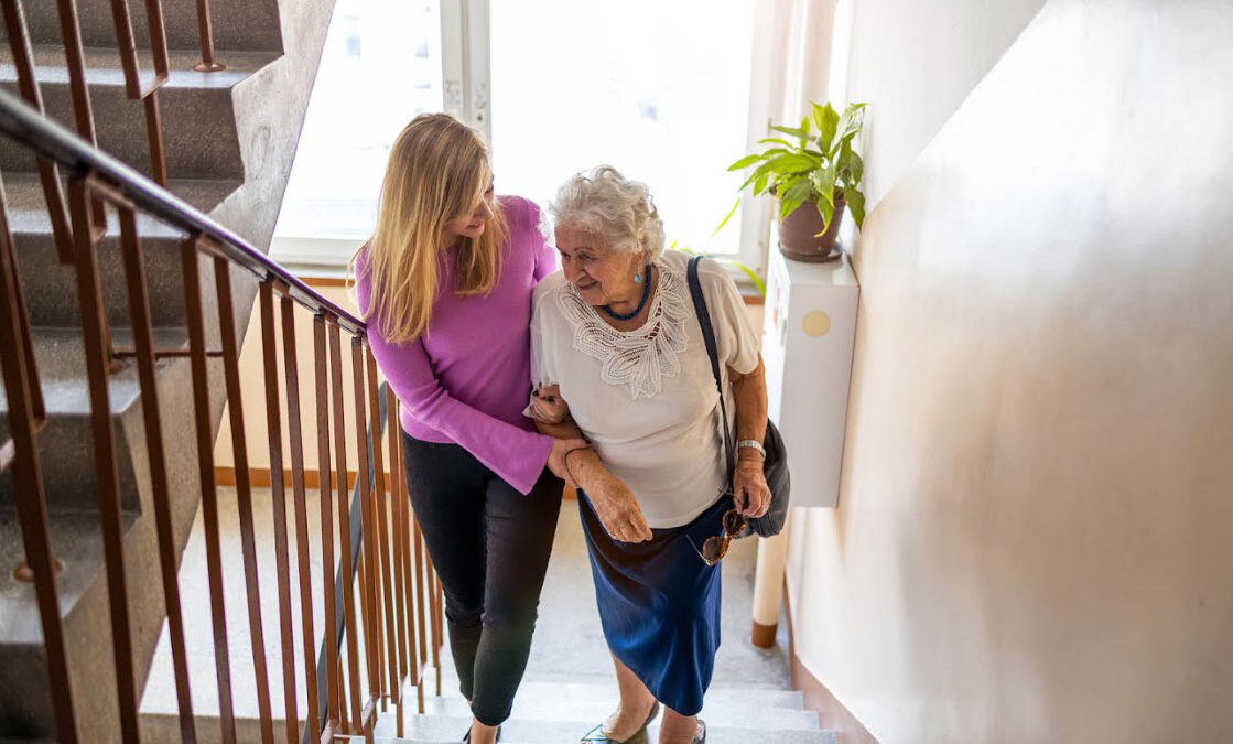 caregiver helping woman up stairs