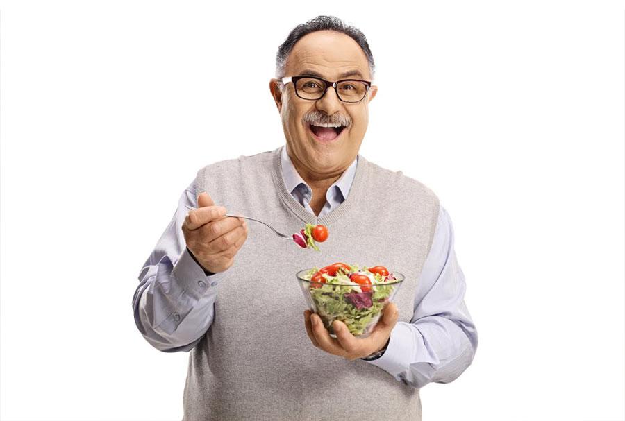 man smiling as he eats salad